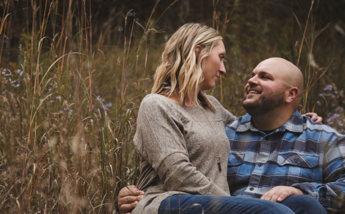 moody engagement pictures in a field with wild flowers near St. Peter Mn