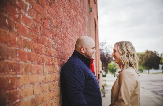 a couple next to historic brick buildings for their engagement photos in St. Peter Mn